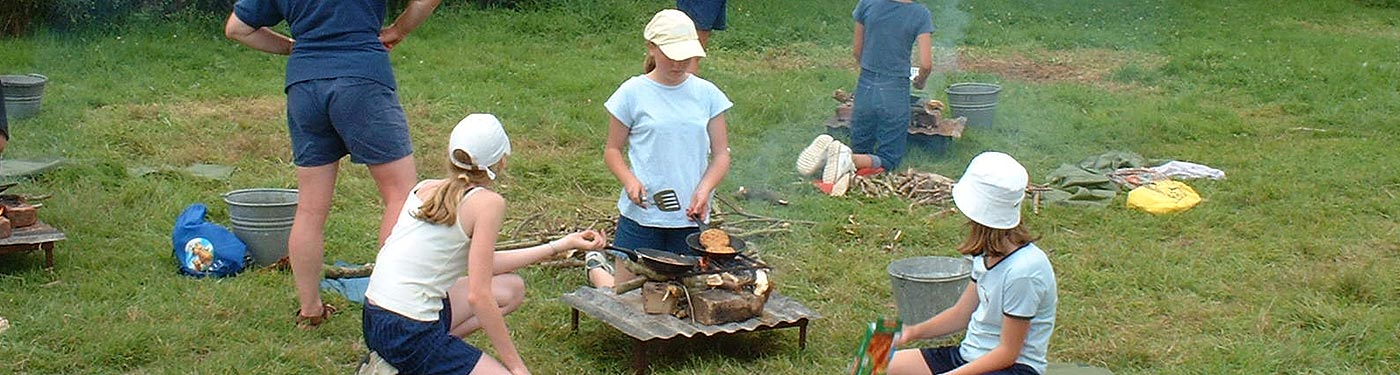 girl guides cooking lunch at campsite